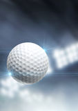 Ball Flying Through The Air. A regular golf ball flying through the air on an indoor stadium background during the night royalty free stock images