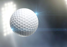 Ball Flying Through The Air. A regular golf ball flying through the air on an a outdoor stadium background during the night stock image