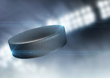 Ball Flying Through The Air. A regular ice hockey puck flying through the air on an indoor stadium background during the night stock photo