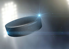 Ball Flying Through The Air. A regular ice hockey puck flying through the air on an a outdoor stadium background during the night stock image