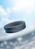 Ball Flying Through The Air. A regular ice hockey puck flying through the air on a stadium background during the daytime royalty free stock images