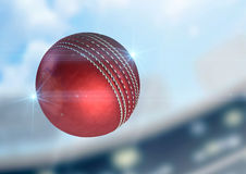 Ball Flying Through The Air. A regular red cricket ball flying through the air on a stadium background during the daytime stock photos