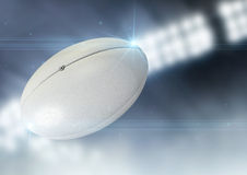 Ball Flying Through The Air. A regular rugby ball flying through the air on an indoor stadium background during the night royalty free stock photography