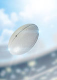Ball Flying Through The Air. A regular rugby ball flying through the air on a stadium background during the daytime stock image