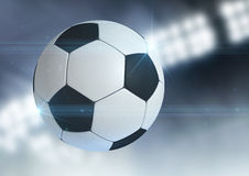 Ball Flying Through The Air. A regular soccer ball flying through the air on an indoor stadium background during the night stock photography