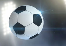 Ball Flying Through The Air. A regular soccer ball flying through the air on an a outdoor stadium background during the night royalty free stock photography