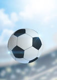 Ball Flying Through The Air. A regular soccer ball flying through the air on a stadium background during the daytime stock photos