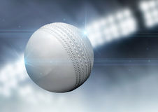 Ball Flying Through The Air. A regular white cricket ball flying through the air on an indoor stadium background during the night royalty free stock photography