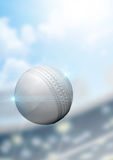 Ball Flying Through The Air. A regular white cricket ball flying through the air on a stadium background during the daytime stock images