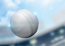 Ball Flying Through The Air. A regular white cricket ball flying through the air on a stadium background during the daytime royalty free stock photography