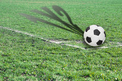Ball on a football field with shadow showing possible score. A ball on a soccer field with shadow showing possible score at the end of the game as background for Stock Photos