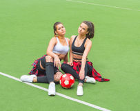 With the ball on the football field two sports girls. Royalty Free Stock Photo