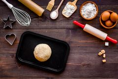 Ball of fresh raw dough near ingedients and cookware on dark wooden background top view.  Royalty Free Stock Images