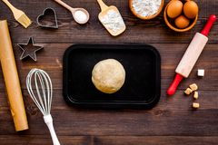 Ball of fresh raw dough near ingedients and cookware on dark wooden background top view.  Stock Photos