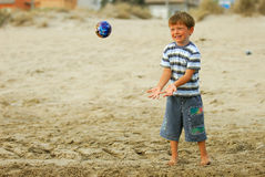Ball games. Boy child is playing with his new ball at the beach royalty free stock photography