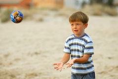 Ball games. Boy child tries to catch his new ball at the beach stock photos