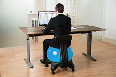 Ball Geschäftsmann-In Front Of Computer Sitting On Pilates Lizenzfreie Stockbilder