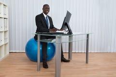 Ball Geschäftsmann-Working Sitting Ons Pilates stockfoto