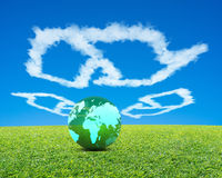 Ball with global map with meadow, recycling shape clouds, sky. Big Green Ball with world wide map in recycling symbol shape clouds, fresh green meadow and blue Royalty Free Stock Photo