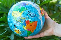 Ball globe in hand. The ball with the image of the globe in the female hand royalty free stock photography