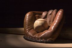 Ball and Glove. Antique baseball glove with a ball, and a bat in the background stock photo