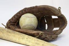 Ball in glove. Bat beside ball in glove royalty free stock photo
