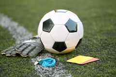 Ball, gloves, whistle and cards on soccer field Stock Photos