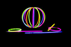 Ball with glow sticks fluorescent lights. Ball, bracvelet, Glow sticks neon light fluorescent on back background. variation of different colored chem lights like Stock Photo