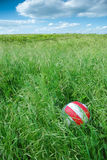 Ball in grass at picnic. Red and white ball in the grass, with white clouds on blue sky in the background. Playground for a perfect picnic in nature Royalty Free Stock Photos