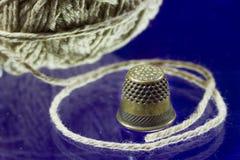 Ball of gray thread and thimble Stock Photos