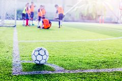 Ball on green artificial turf at corner of football field with b. Lurry players are training background. Soccer training or football training royalty free stock image