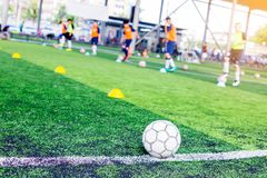 Ball on green artificial turf at side line of football field wit. H blurry players are training background. Soccer training or football training royalty free stock photography