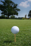 Ball on Green with Golfer. Golfball on a tee with a golfer in the distance Stock Images