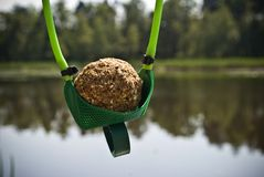 Ball of groundbait in slingshot ready to shoot and feed fish.  stock photos
