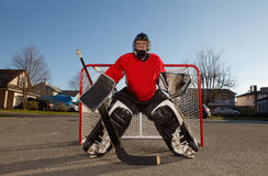 Ball hockey goalie outside in net. A teenage boy dressed to be the goalie in a street hockey game stock images