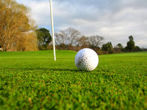 The Ball and The Hole #2. Shot of golfers shoes, iron & ball...ready to go for the putt stock image