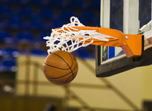 Ball in the hoop. Basketball ball falling through the hoop Stock Image
