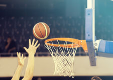 Ball in hoop at basketball game Royalty Free Stock Images