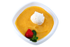 Ball of ice cream floats in mango puree, on white. Stock Image