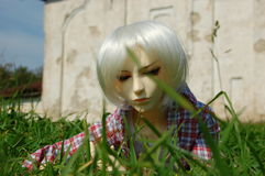 Ball-jointed doll with squinting glance lying. There is ball-jointed doll with squinting glance lying on the grass stock images