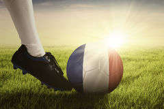 Ball kicked by football player on the grass. Soccer ball kicked by foot of football player at the field with sunlight background Royalty Free Stock Image