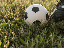Ball at the kickoff of a football or soccer game. Natural sunset light. Grass background stock images