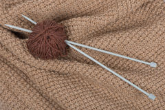Ball , knitted pattern and knitting needles. Clew and needles on beige  knitted pattern Stock Photography
