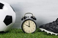 Ball and leather boots for playing football next to the clock on a green background of grass royalty free stock images