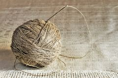 Ball of linen threads with big needle on handmade gray tablecloth. Close up Royalty Free Stock Image