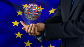 Ball made of European nationals flags turning on hands in front of European flag stock video footage
