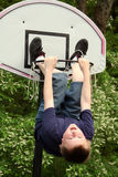 The Ball, Not You. Preteen boy hanging from a basketball net, with his legs through the hoop stock photography