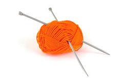 Ball of orange wool with knitting needles on white Stock Photos