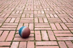 Ball on a pavement tiles Royalty Free Stock Images