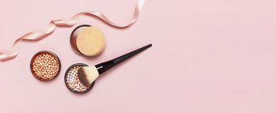Ball pearl blush, face powder, makeup brush and pink ribbon on a pastel pink background top view Flat Lay with copy space. Various. Cosmetic products, Makeup royalty free stock photography